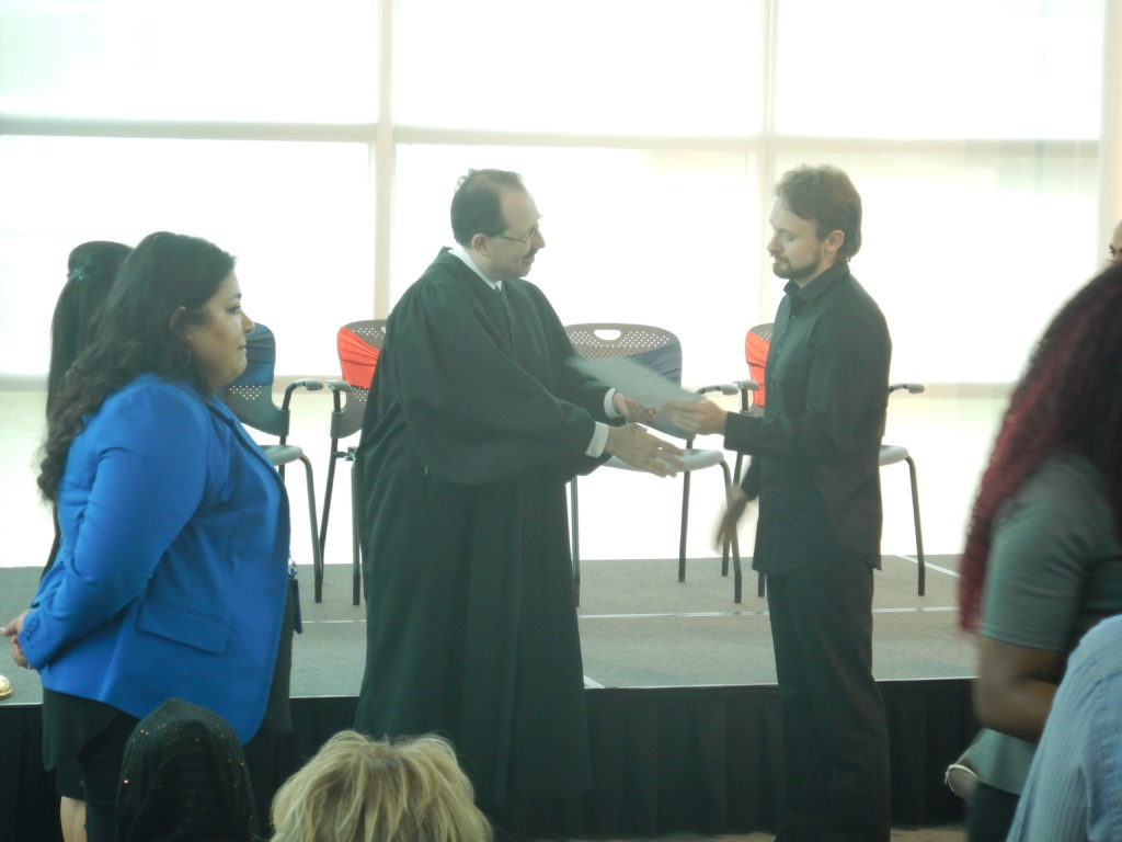 Mike, receiving his diploma from the judge at the citizenship ceremony.